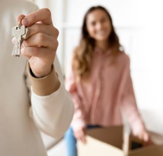 main tenant des clés et femme souriante en arriere plan