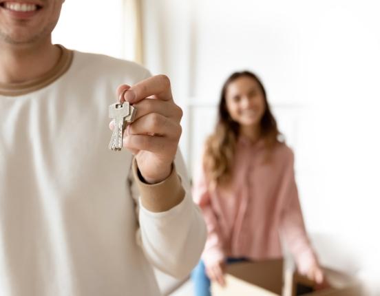 photo homme avec des clés dans la main et femme en arrière plan