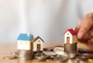 Image d'illustration représentant un tas de pièces sur une table et trois petites maisons en figurine dont l'une est tenue par une main d'homme