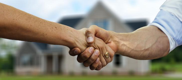 Image d'illustration représentant une poignée de main entre un homme et une femme devant une maison
