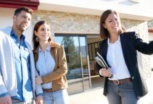 Image d'illustration représentant un promoteur immobilier qui tend la main pour indiquer l'extérieur d'une maison à un couple souriant