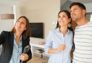 Image d'illustration représentant un promoteur immobilier montrant les détails d'un salon d'une maison à un couple souriant