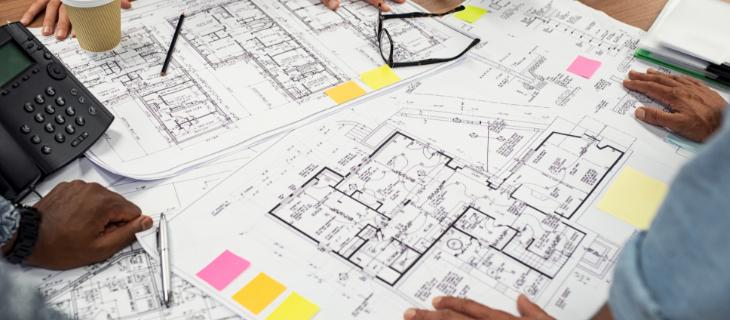 Image d'illustration représentant une table vue de haut où des plans d'appartements et de maisons sont entreposés