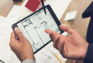 Image d'illustration représentant un homme debout tenant une tablette tactile avec un plan d'appartement et montrant le bleu