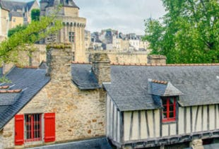 Photographie des lavoirs de Vannes se trouvant devant la Garenne et des remparts et de la veille ville de Vannes en second plan sous un ciel nuageux