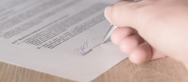 Image d'illustration représentant un contrat en train d'être signé par un homme