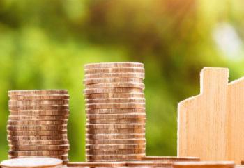 Image d'illustration représentant des empilements de pièces de monnaie et une petite maison en bois