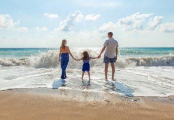 Image d'illustration représentant une famille qui a les pieds dans l'eau sur la plage