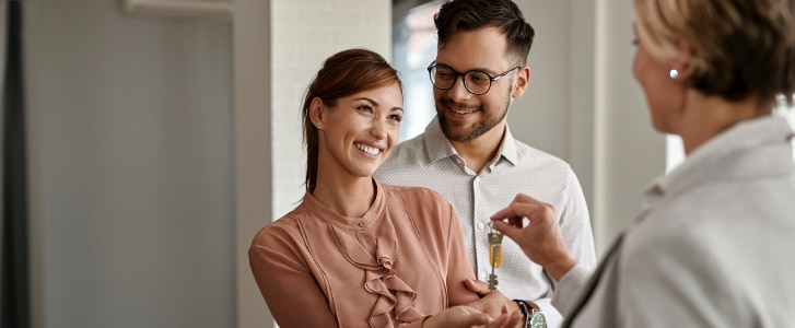 Image d'illustration représentant un couple souriant recevant des clés d'appartement de la part d'un promoteur immobilier